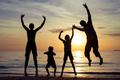 Silhouette of happy family who playing on the beach at the sunse