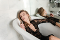 Young woman smoking and lying in bath