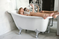 Full-length shot of woman with shower lying in bath