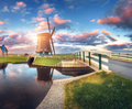Windmill and bridge near the water canal at sunrise