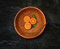The oranges citrus fruit halves on wooden plate