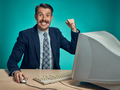 Portrait of cheerful young businessman sitting with computer