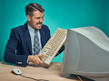 Angry businessman breaking keyboard against blue background