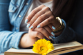 Girl's hands on a book with a yellow flower
