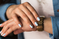 Stylish girl with a blue manicure and a golden clock. Fashion, lifestyle, beauty, clothing.