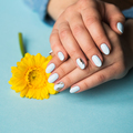 Girl with blue manicure holds a yellow flower