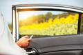 Travelers checks mobile phones on car.