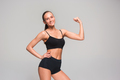 Muscular young woman athlete on gray