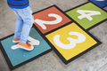 Young kid playing hopscotch