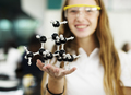 Student girl holding molecule on her hand