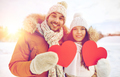happy couple with red hearts over winter landscape