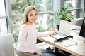 Cheerful lady sitting in office coworking using laptop
