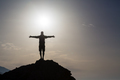 Man with arms outstretched celebrate mountains sunrise