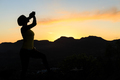 Woman climbing success silhouette in mountains sunset