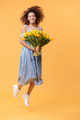 Full-length portrait of  African woman jumping with bouquet  flo