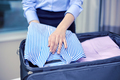 businesswoman packing clothes into travel bag