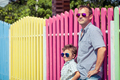 Father and son standing near the multicolored fence at the day t