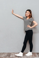 Happy young asian lady over grey wall make stop gesture