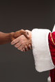The handshake of Santa Claus hand and hand of african man