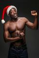 Muscular black shirtless young man in Santa Claus hat