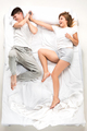 The young lovely couple lying in a bed with alarm clock