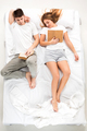 The young lovely couple lying in a bed with books