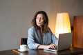 Thinking concentrated woman writer sitting indoors using laptop