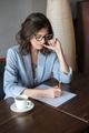 Thinking woman writer sitting indoors