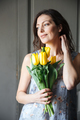 Happy woman writer sitting indoors while holding tulips.