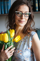 Smiling woman writer sitting indoors while holding tulips.