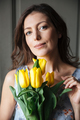 Happy woman writer sitting indoors while holding tulips