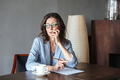 Thoughtful woman writer sitting indoors