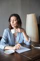 Thinking serious woman writer sitting indoors