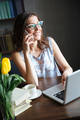 Beautiful woman writer sitting indoors while talking by phone