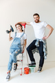 Pretty couple with repair equipment standing near ladder