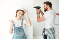 While man using drill his woman posing