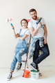 Cheerful lovers looking camera while sitting on ladder isolated