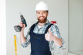 Portrait of bearded man builder with drill and thumb up