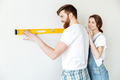 Young loving couple standing in new flat make repair.