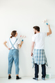 Full length back view of young beautiful couple painting