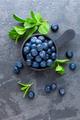 Fresh Blueberries in a bowl on dark background, top view. Juicy wild forest berries, bilberries