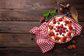Delicious strawberry pie with fresh blueberry and whipped cream on wooden rustic table
