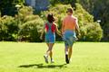 happy teenage couple walking at summer park