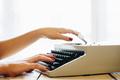 Girls hands typing in vintage typewriter