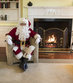 smiling santa claus by fireplace