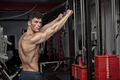 Attractive muscular guy exercising in the gym