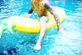 Caucasian tattooed man floating in the swimming pool by inflatab