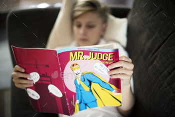 Young caucasian man lying on the couch reading cartoon