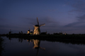 Windmills along the canal water at twilight
