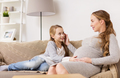 happy pregnant woman and girl on sofa at home